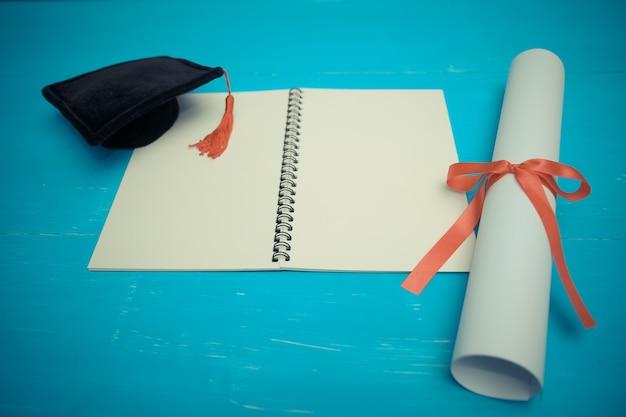 Diploma com fita vermelha e boné de formatura preto na madeira