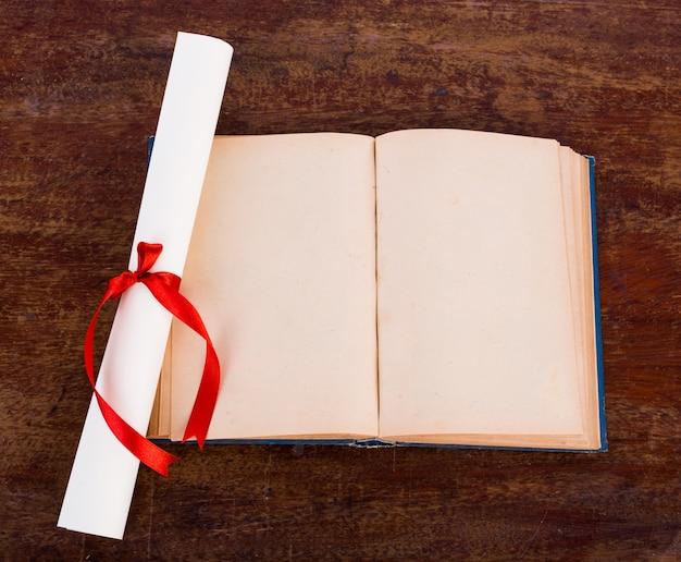Diploma com livro velho isolado em um fundo branco.