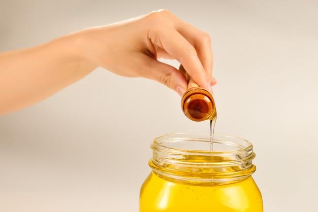 Dipper com mel na mão da mulher. espaço para texto ou desenho.