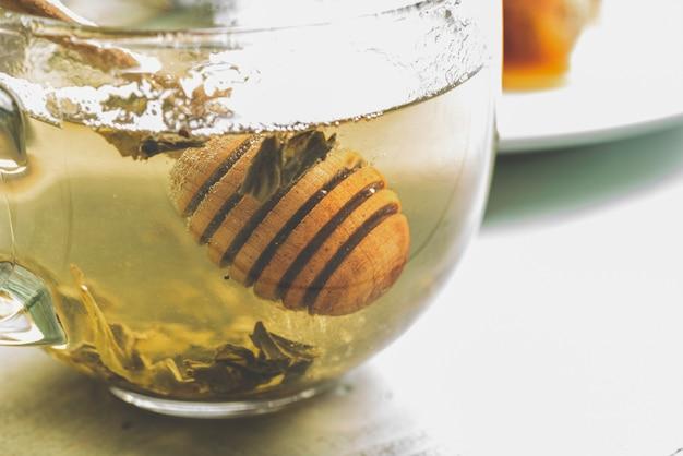 Dipper de mel em xícara de chá verde