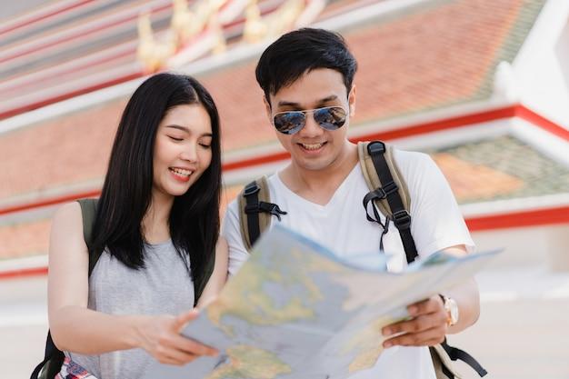 Direção de casal asiático viajante no mapa de localização em bangkok, tailândia