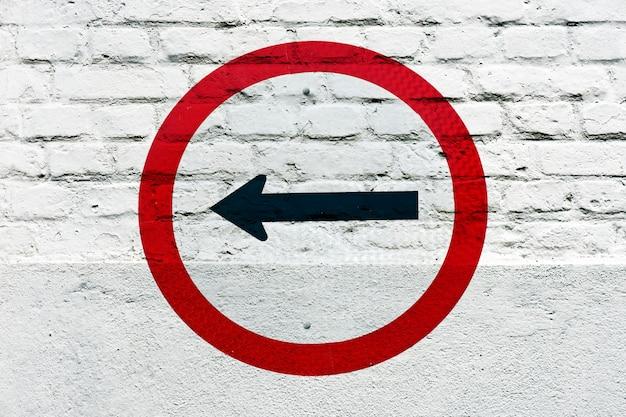 Direção obrigatória: sinal de trânsito estampado na parede branca, como graffiti
