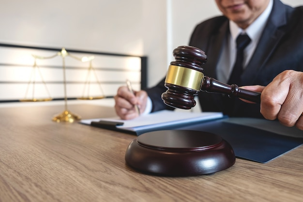Direito legal, conceito de aconselhamento e justiça, advogado conselheiro ou notário trabalhando em documentos e relatório do caso importante e martelo de madeira, escala de latão na mesa na sala de audiências