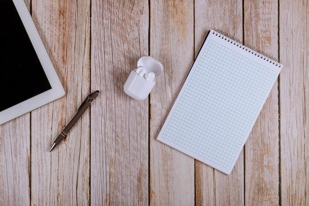 Diretamente acima da vista de uma velha mesa de madeira, escritório digital tablet pc, caneta de fones de ouvido sem fio, notebook