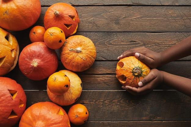 Diretamente de cima, vista plana de abóboras esculpidas e tangerinas com cara de jack o 'lantern e mãos de mulher segurando uma abóbora para o halloween na superfície da mesa de madeira escura.