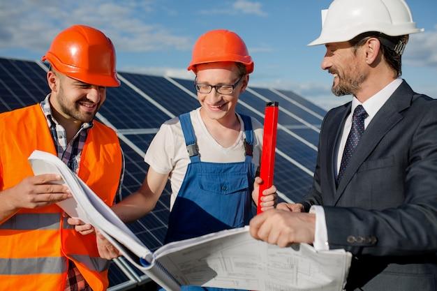 Diretor, capataz e trabalhador que olha em desenhos técnicos na estação de energia solar.