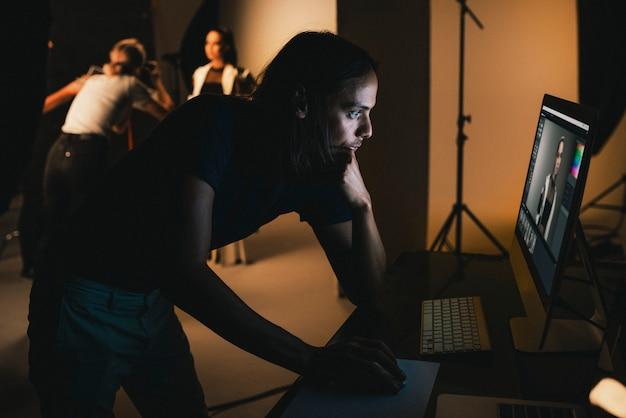 Diretor de arte, verificando fotos em um monitor
