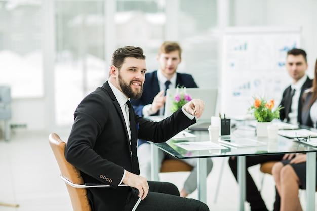 Diretor e equipe de negócios discutem a apresentação de um novo projeto financeiro em um moderno escritório.