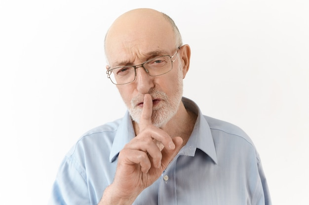 Diretor executivo idoso estrito e irritado, de camisa azul e óculos, fazendo sinal de silêncio durante a conferência, pedindo para falar baixinho. homem sênior segurando o dedo da frente junto aos lábios, dizendo shh