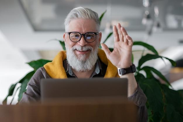 Diretor ou gerente sênior bonito de cabelos grisalhos trabalhando com um laptop e conversando online