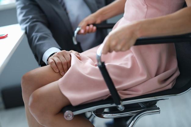 Diretor segurando com a mão no joelho da secretária sentada à mesa em close do escritório