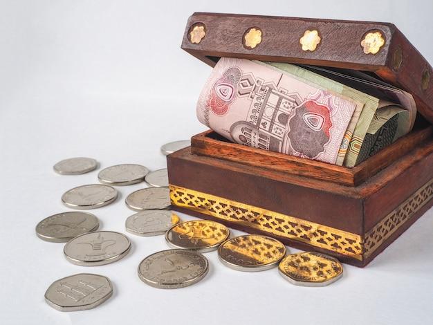Dirhams de dinheiro árabe na caixa de madeira velha.