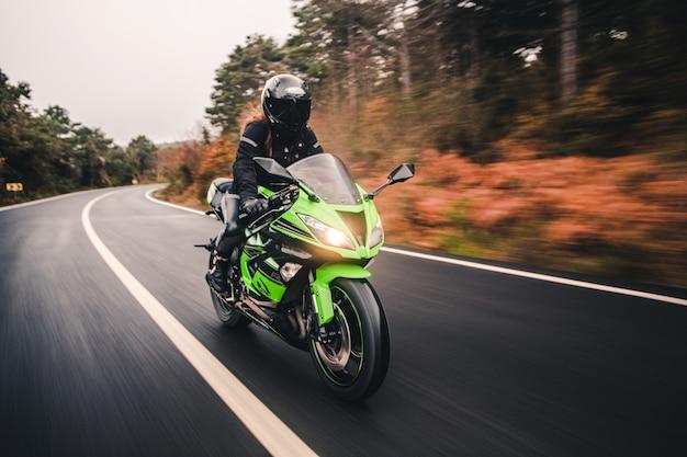 Dirigindo a motocicleta de cor verde neon na estrada.