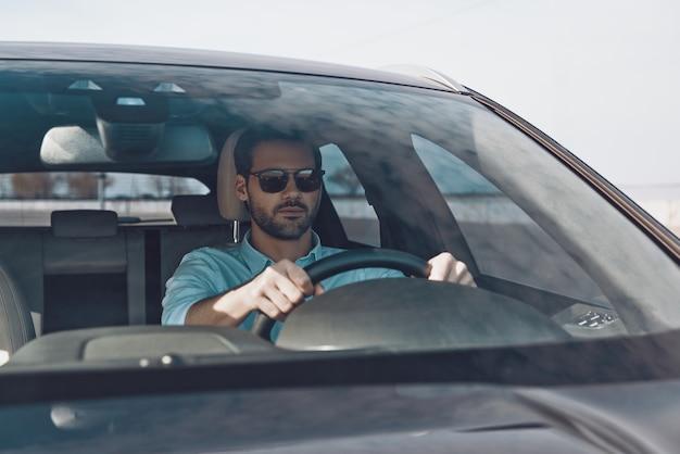 Dirigindo com cuidado. jovem bonito olhando direto enquanto dirige um carro de status