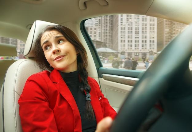 Dirigindo pela cidade. jovem mulher atraente dirigindo um carro.