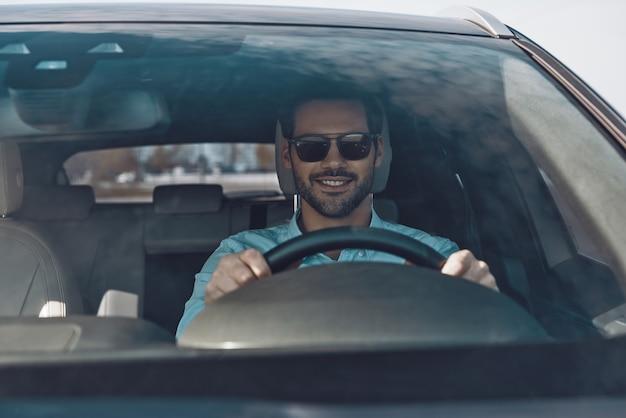 Dirigindo seu carro novo. jovem bonito sorrindo enquanto dirige um carro de status
