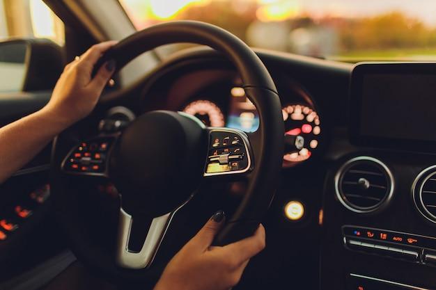 Dirigindo um carro à noite - bonita, jovem mulher dirigindo seu carro moderno à noite em uma cidade dof rasa imagem em tons de cor.