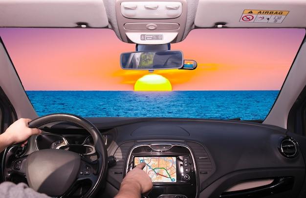 Dirigir um carro usando a tela de toque de um sistema de navegação gps em direção a um belo pôr do sol no mar mediterrâneo, itália