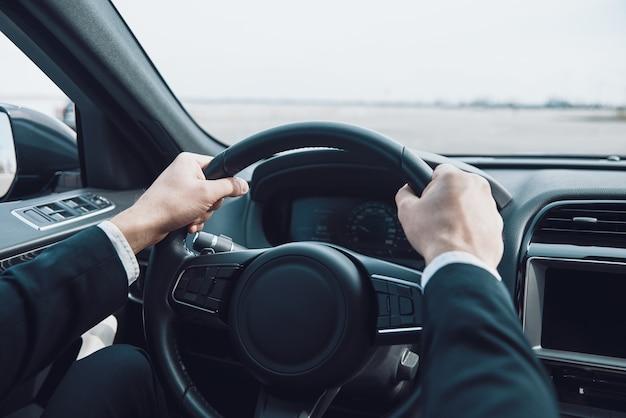 Dirija com cuidado! close-up de um homem mantendo as mãos no volante enquanto dirige um carro