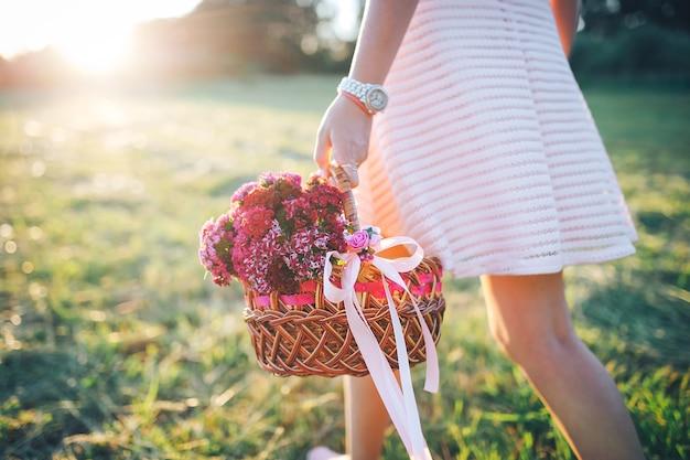 Dirl com uma cesta de flores em um vestido rosa