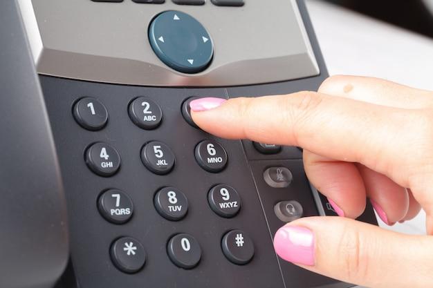 Discando o telefone voip nos detalhes do escritório, teclado e monitor