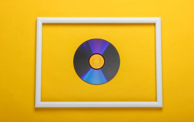 Disco de cd em moldura branca em superfície amarela