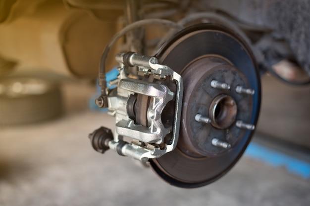 Disco de freio de roda de carro e sapatos de automóvel levantada na estação de serviço de reparação