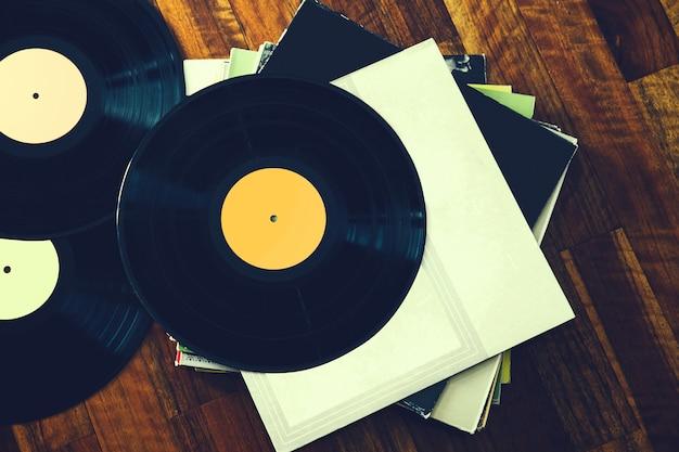 Disco de vinil antigo e uma coleção de álbuns em fundo de madeira imagem tonificada