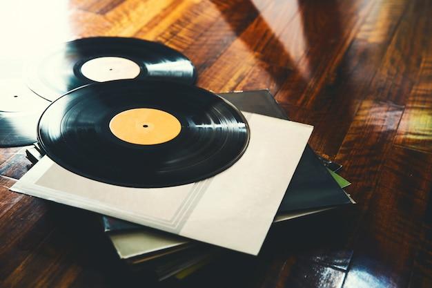 Disco de vinil antigo e uma coleção de álbuns em fundo de madeira