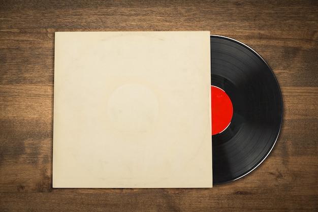 Disco de vinil com capa em branco na mesa de madeira