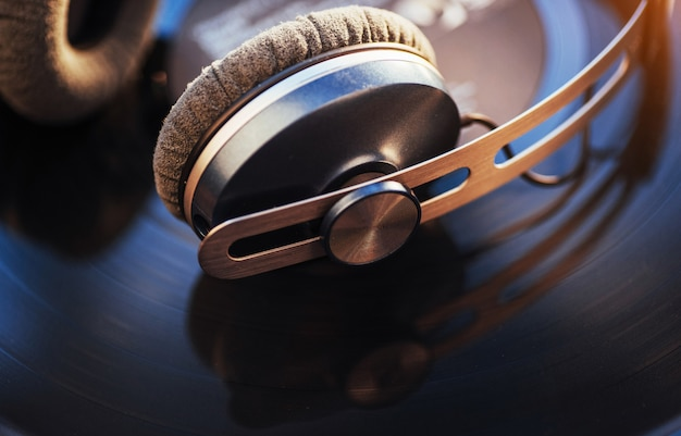 Disco de vinil e fone de ouvido sobre a mesa de madeira