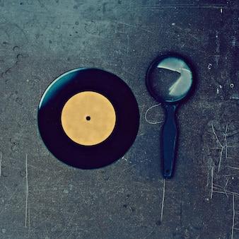 Disco de vinil e lupa na mesa de madeira
