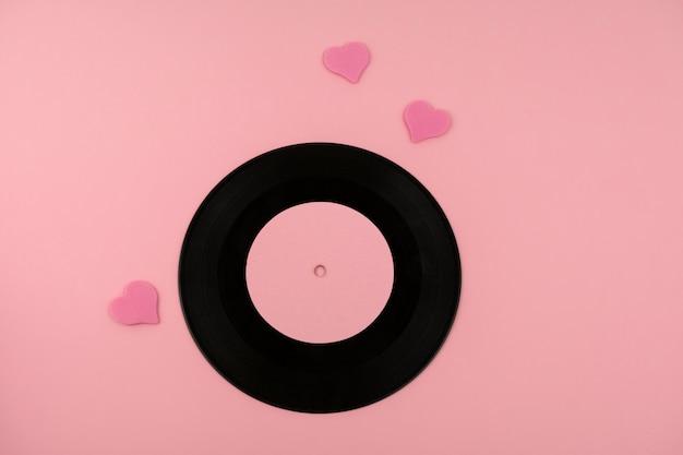 Disco de vinil empoeirado retrô com músicas favoritas e corações rosa em rosa