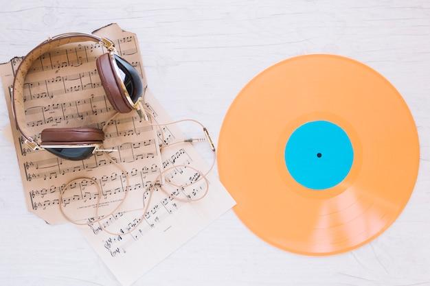 Disco de vinil perto de fones de ouvido e partituras