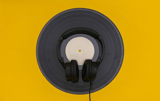 Disco de vinil retrô e fones de ouvido estéreo em fundo amarelo. vista do topo