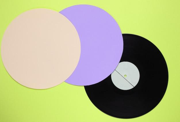 Disco de vinil retrô em um fundo de cor verde com círculos roxos amarelos. minimalismo retro. vista do topo
