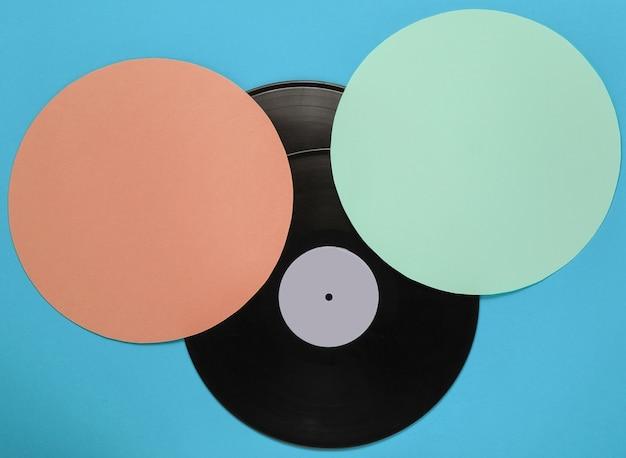 Disco de vinil retrô sobre fundo de cor azul com círculos verdes laranja. minimalismo retro. vista do topo
