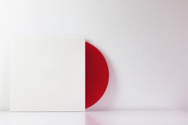 Disco de vinil vermelho, na caixa branca, com espaço em branco para escrever.