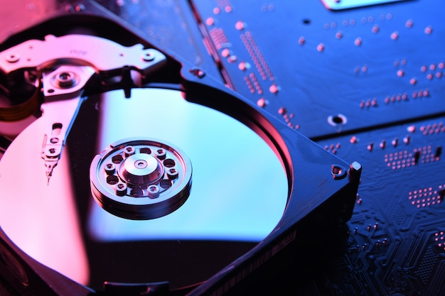 Disco rígido de computador drives hdd, ssd na placa de circuito, mesa da placa-mãe. fechar-se. com iluminação vermelho-azulada.