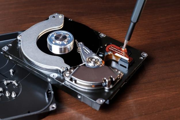 Disco rígido do computador com uma chave de fenda na área de trabalho