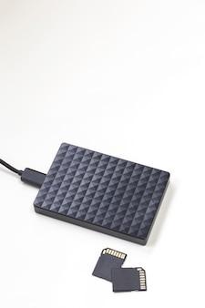 Disco rígido externo preto do dispositivo de armazenamento e cartões sd isolados no computador de parede branco
