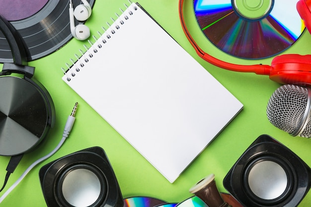 Discos compactos; alto falante; fone de ouvido; fone de ouvido ao redor do bloco de notas em espiral sobre fundo verde