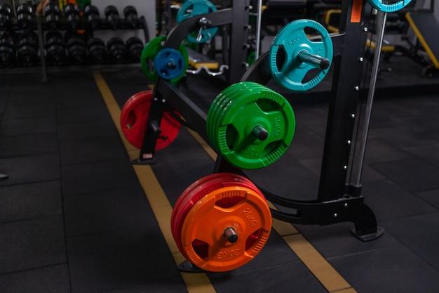 Discos de barra coloridos em prateleiras em uma academia moderna