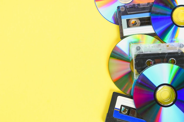 Discos de cd e cassetes de áudio em um fundo pastel amarelo. minimalismo.