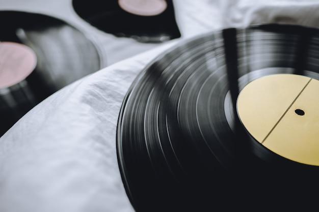 Discos de vinil antigos em uma cama branca.
