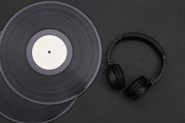 Discos de vinil retrô e fones de ouvido em um fundo preto. vista do topo