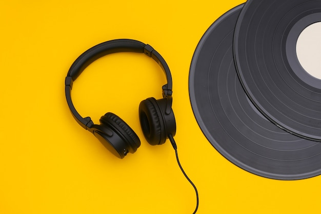 Discos de vinil retrô e fones de ouvido estéreo em fundo amarelo. vista do topo