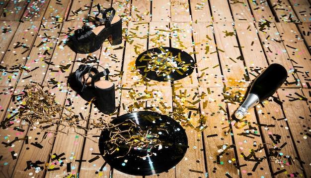 Discos de vinil, sapatos de mulher e uma garrafa de bebida entre confetes