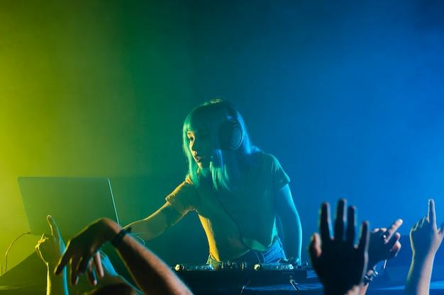 Discoteca com luzes coloridas e dj feminino