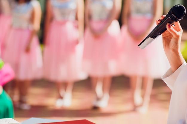 Discurso de cerimônia mestre no microfone fundo casal de noivos. microfone no fundo das damas de honra